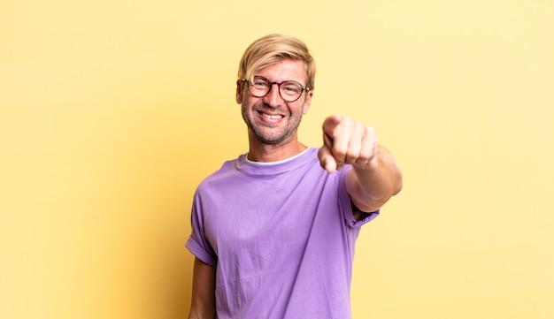 Przystojny blond dorosły mężczyzna wskazujący na kamerę z zadowolonym, pewnym siebie, przyjaznym uśmiechem, wybierający ciebie