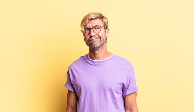 Przystojny blond dorosły mężczyzna wyglądający na zdziwionego i zdezorientowanego, zastanawiający się lub próbujący rozwiązać problem lub myślący