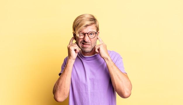 Przystojny blond dorosły mężczyzna wyglądający na zły, zestresowany i zirytowany, zakrywający obydwa uszy ogłuszającym hałasem, dźwiękiem lub głośną muzyką