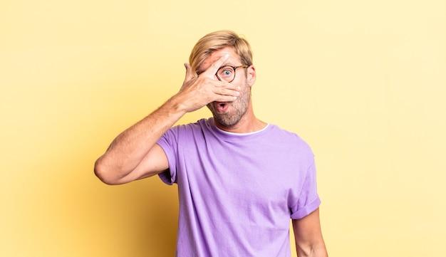 Przystojny blond dorosły mężczyzna wyglądający na zszokowanego, przestraszonego lub przerażonego, zakrywający twarz dłonią i zerkający między palcami