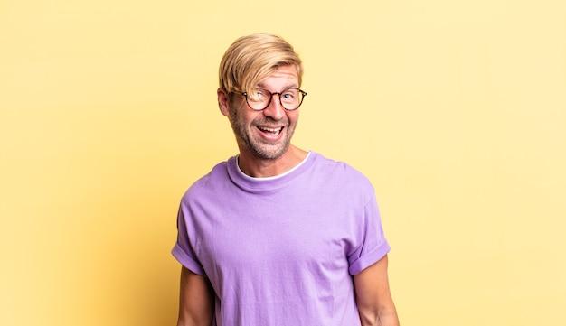 Przystojny blond dorosły mężczyzna z dużym, przyjaznym, beztroskim uśmiechem, wyglądający pozytywnie, zrelaksowany i szczęśliwy, przerażający