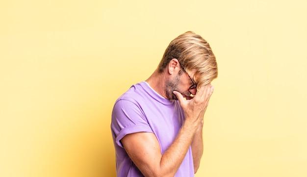 Przystojny blond dorosły mężczyzna zakrywający oczy dłońmi ze smutnym, sfrustrowanym wyrazem rozpaczy, płaczu, widoku z boku