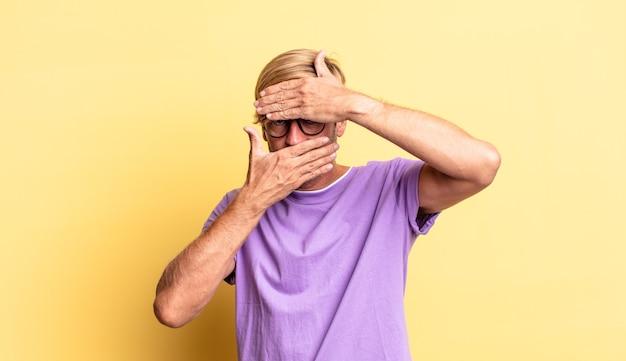 Przystojny blond dorosły mężczyzna zakrywający twarz obiema rękami mówiąc nie do kamery! odmowa robienia zdjęć lub zabranianie zdjęć