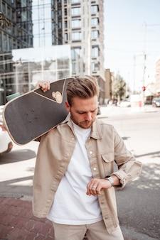 Przystojny blond młody człowiek deskorolkarz trzymając longboard na ramieniu patrząc poważnie na zegarek w pośpiechu na tle budynku miejskiego. nosi swobodny beżowy strój dżinsowy. koncepcja wypoczynku na zewnątrz.
