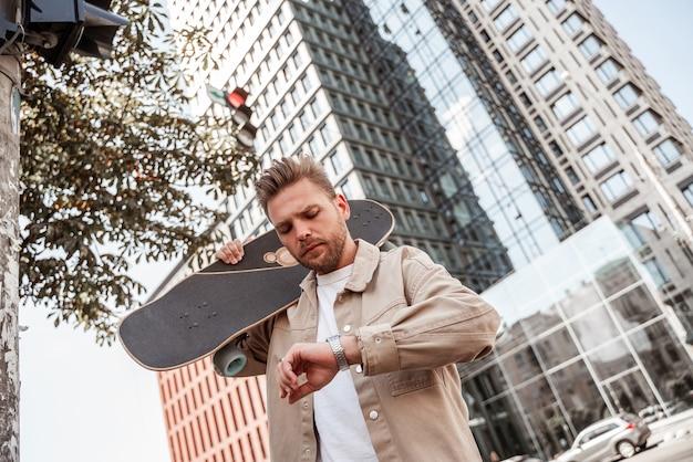 Przystojny blond młody człowiek deskorolkarz trzymając longboard na ramieniu w pośpiechu, patrząc poważnie na zegarek. w ruchu miejskim tle budynku. nosi beżową dżinsową koszulę. wypoczynek na świeżym powietrzu. dojeżdżać