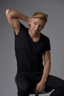 Przystojny blond młody człowiek pozuje przy studiiem
