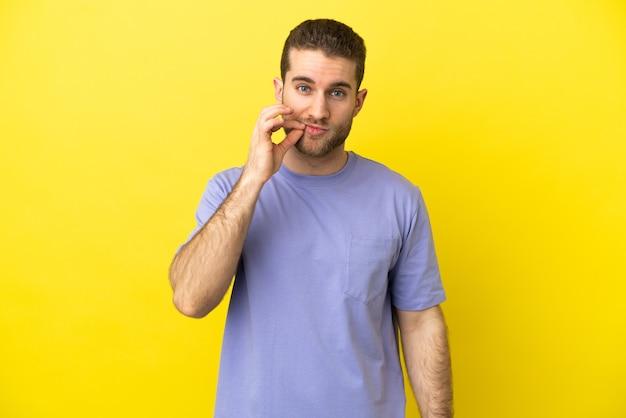 Przystojny blondyn na na białym tle żółtym tle pokazujący znak gestu ciszy