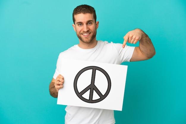 Przystojny blondyn na odosobnionym niebieskim tle, trzymający afisz z symbolem pokoju i wskazujący go