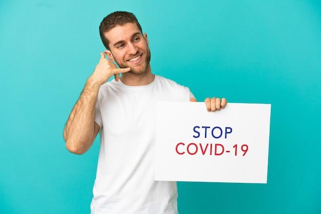 Przystojny blondyn na odosobnionym niebieskim tle, trzymający afisz z tekstem stop covid 19 i wykonujący gest telefoniczny