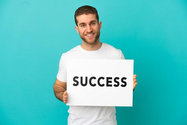 Przystojny blondyn na odosobnionym niebieskim tle, trzymający afisz z tekstem sukces ze szczęśliwym wyrazem twarzy