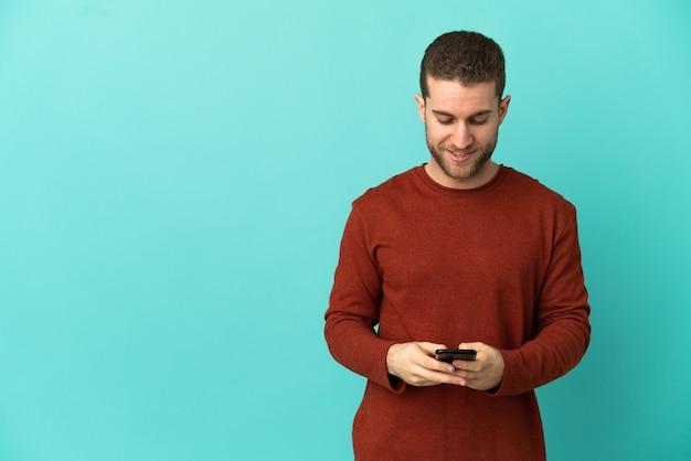Przystojny blondyn na odosobnionym niebieskim tle wysyła wiadomość za pomocą telefonu komórkowego