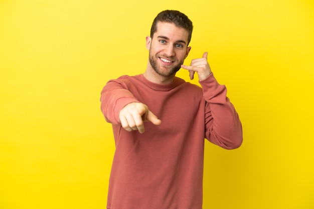 Przystojny blondyn na odosobnionym żółtym tle robi gest telefonem i wskazuje przód