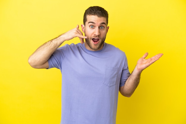 Przystojny blondyn na odosobnionym żółtym tle robiący gest telefoniczny i wątpiący