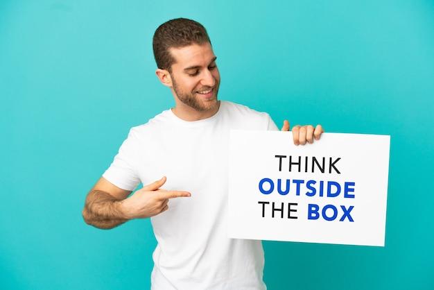 Przystojny blondyn na pojedyncze niebieskie tło trzyma tabliczkę z tekstem think outside the box i wskazuje go