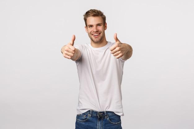 Przystojny blondyn o niebieskich oczach i białej koszulce daje kciuki do góry