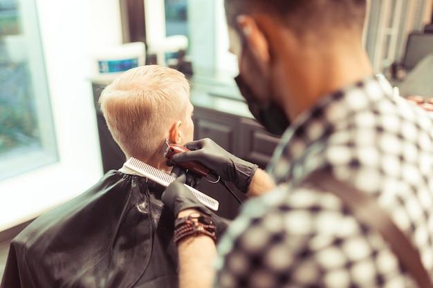 Przystojny blondyn obcięty przez fryzjera w salonie fryzjerskim retro, widok z tyłu