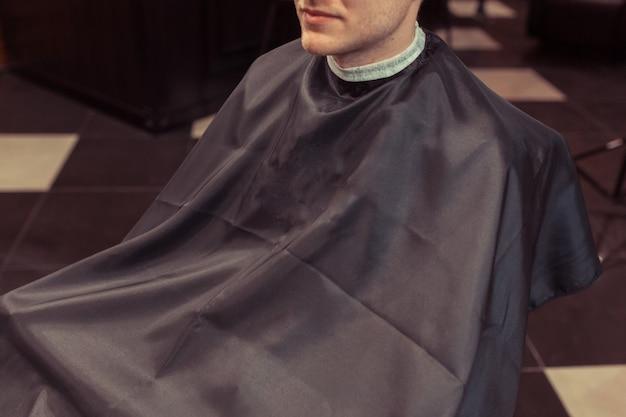 Przystojny blondyn obcięty przez fryzjera w salonie fryzjerskim retro
