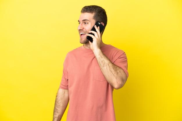 Przystojny blondyn używający telefonu komórkowego na białym tle, śmiejący się w pozycji bocznej