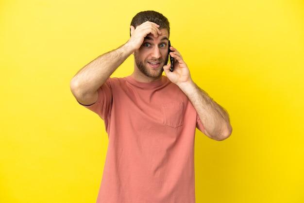 Przystojny blondyn używający telefonu komórkowego na na białym tle, robiący gest zaskoczenia, patrząc w bok