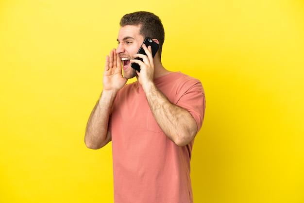 Przystojny blondyn używający telefonu komórkowego na odosobnionym tle krzyczy z szeroko otwartymi ustami