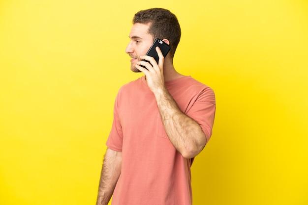 Przystojny blondyn używający telefonu komórkowego na odosobnionym tle patrząc z boku
