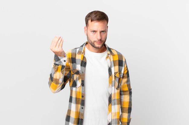 Przystojny blondyn wykonujący gest kaprysu lub pieniędzy, mówiący, żebyś zapłacił