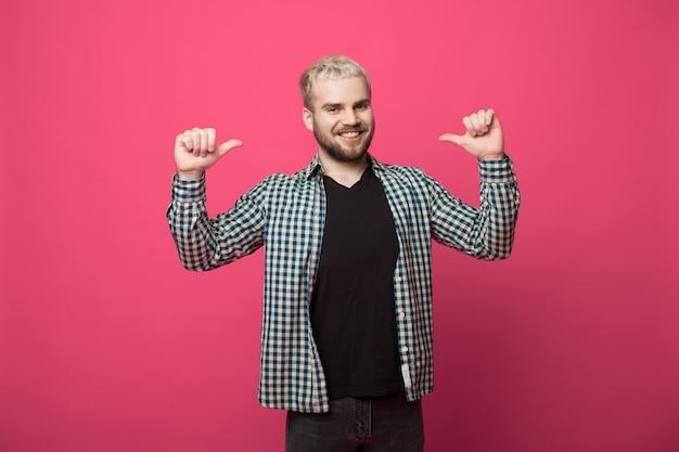 Przystojny blondyn z brodą wskazuje na siebie i uśmiecha się do kamery na czerwonej ścianie studia