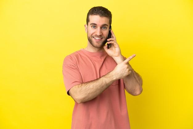 Przystojny blondyn za pomocą telefonu komórkowego na białym tle, wskazując na bok, aby zaprezentować produkt
