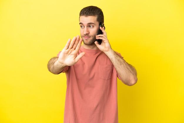 Przystojny blondyn za pomocą telefonu komórkowego na białym tle, wykonując gest zatrzymania i rozczarowany