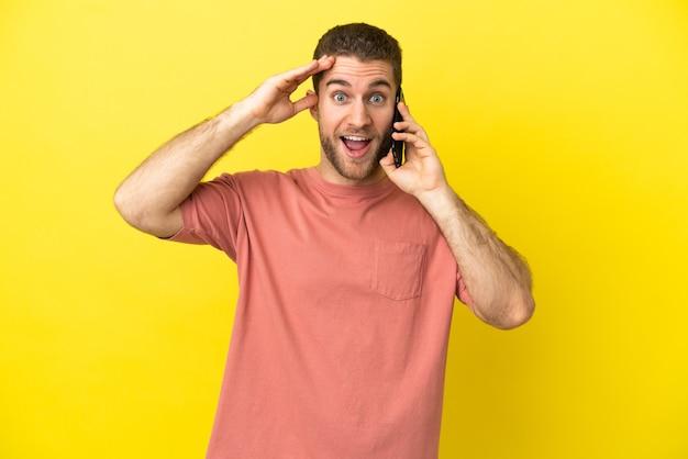 Przystojny blondyn za pomocą telefonu komórkowego na białym tle z wyrazem zaskoczenia