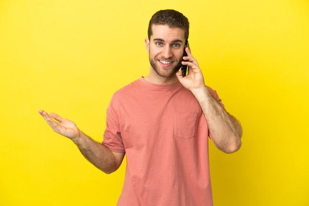 Przystojny blondyn za pomocą telefonu komórkowego na na białym tle, wyciągając ręce do boku, aby zaprosić do siebie