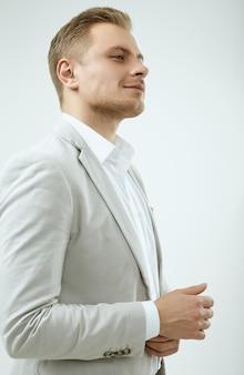 Przystojny blondynka mężczyzna model w szarym kolorze mody w studio