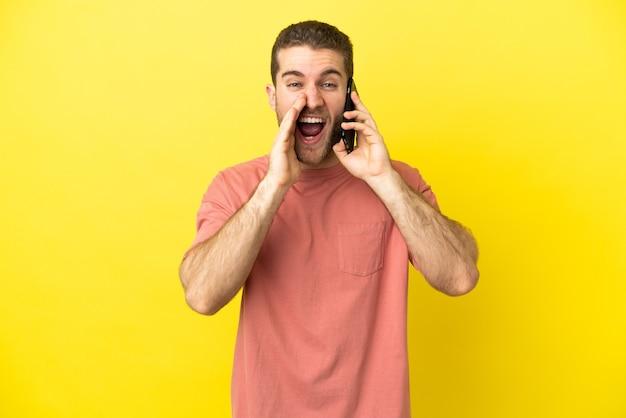 Przystojny blondynka przy użyciu telefonu komórkowego na białym tle krzycząc z szeroko otwartymi ustami