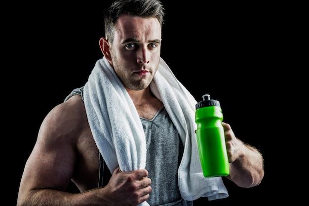 Przystojny bodybuilder z ręcznikiem i butelką