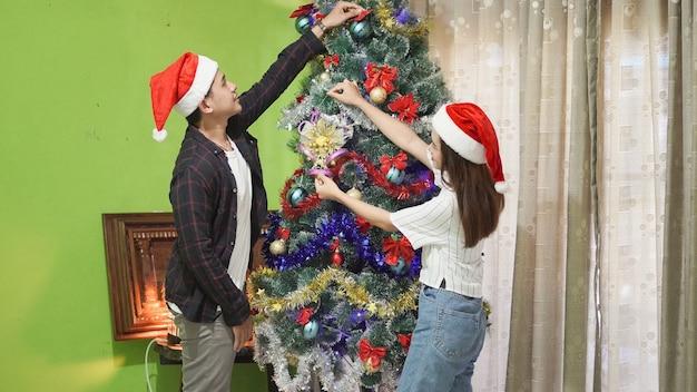 Przystojny brat i piękna siostra wspólnie dekorują choinkę w domu