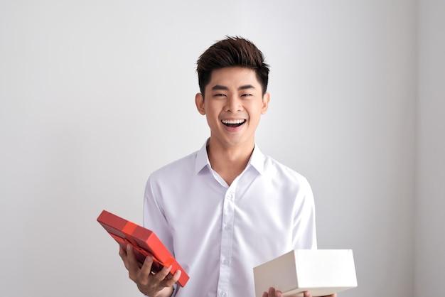 Przystojny broda młody mężczyzna uśmiechający się i otwierający brązowe pudełko, facet ubrany w białą koszulę, na białym tle