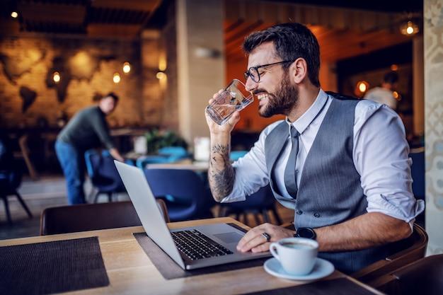 Przystojny brodaty biznesmen kaukaski w garnitur i okulary siedzi w kawiarni, za pomocą laptopa i wody pitnej.