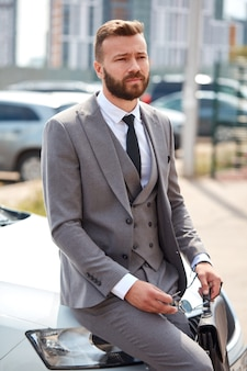Przystojny brodaty biznesmen siedzi na reprezentacyjnej masce samochodu