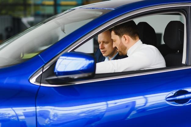 Przystojny brodaty biznesmen siedzi w nowym samochodzie w salonie samochodowym