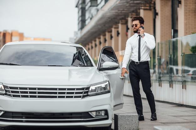 Przystojny brodaty biznesmen w białej koszuli, rozmawiający przez telefon i wsiadający do samochodu, stojąc na zewnątrz na ulicach miasta w pobliżu nowoczesnego centrum biurowego
