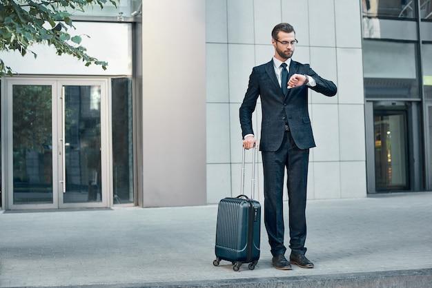 Przystojny brodaty biznesmen w klasycznym garniturze z walizką czeka na taksówkę