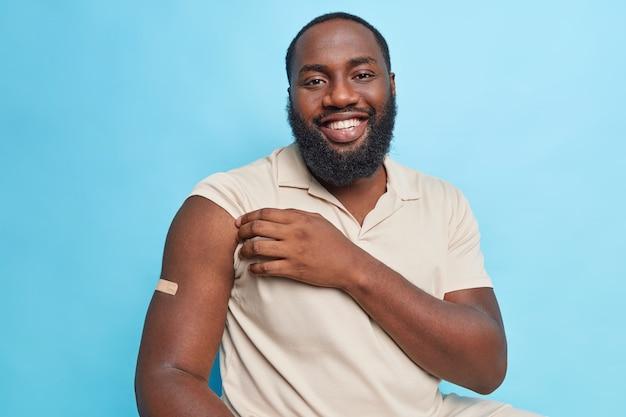 Przystojny brodaty dorosły mężczyzna z ciemną skórą pokazuje ramię po szczepieniu, będąc w dobrym nastroju, czuje się chroniony na białym tle nad niebieską ścianą.