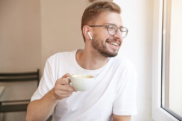 Przystojny brodaty facet patrzy przez okno i pije kawę słuchając muzyki w słuchawkach, ubrany w zwykłe ubranie