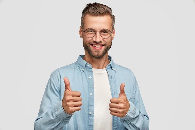 Przystojny brodaty facet pozuje przy białej ścianie