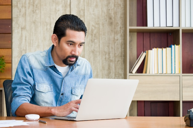Przystojny brodaty facet siedzi przy biurku i używa laptopa.