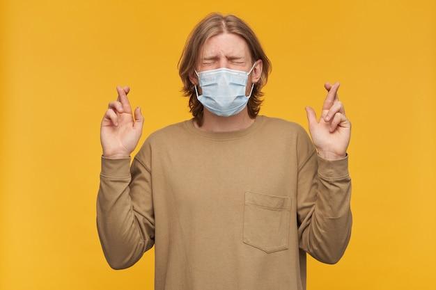 Przystojny brodaty facet z blond fryzurą. noszenie beżowego swetra i medycznej maski ochronnej. mrużki z zamkniętymi oczami. trzyma kciuki, życzę sobie. stań odizolowany na żółtej ścianie