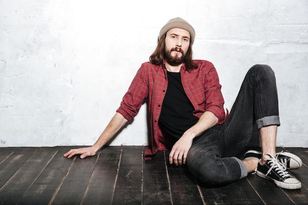 Przystojny brodaty hipster mężczyzna w kapeluszu ubrany w koszulę w klatce, siedzący na podłodze pozowanie na ścianie