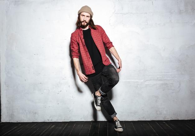 Przystojny brodaty hipster mężczyzna w kapeluszu ubrany w koszulę w klatce stojący pozowanie na ścianie