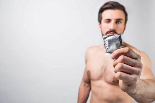 Przystojny brodaty mężczyzna bez koszuli, pokazując prezerwatywę. dobrze jest go używać, aby zapobiegać niespodziewanym złym rzeczom u ludzi. koncepcja reklamy. zapobieganie ciąży. pojedynczo na białej ścianie