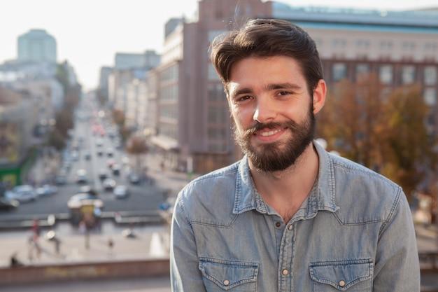Przystojny brodaty mężczyzna cieszy się ciepłego dzień przy miastem